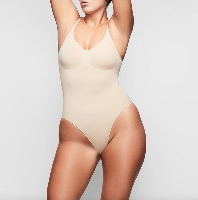 Plus Size model wearing a light nude colored shapewear bodysuit to be worn under wedding dress