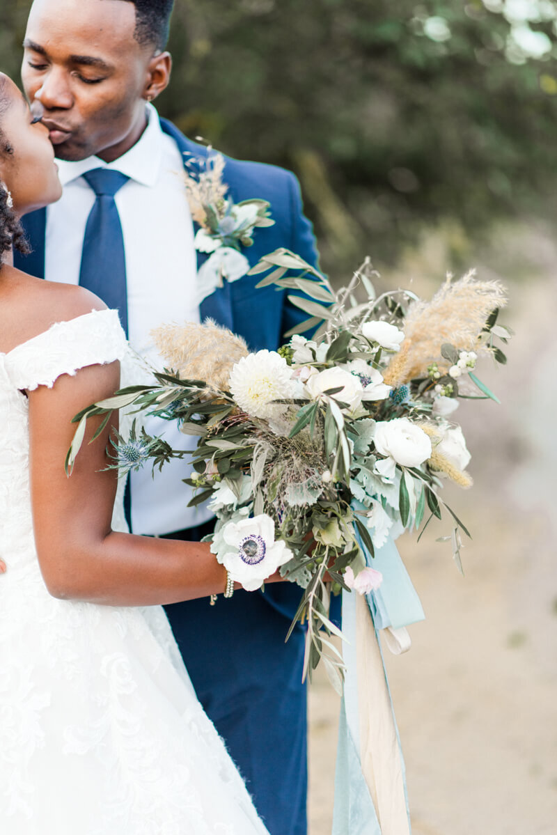 Trendy bride styled photo featuring groom and bride kissing and holding bouquet