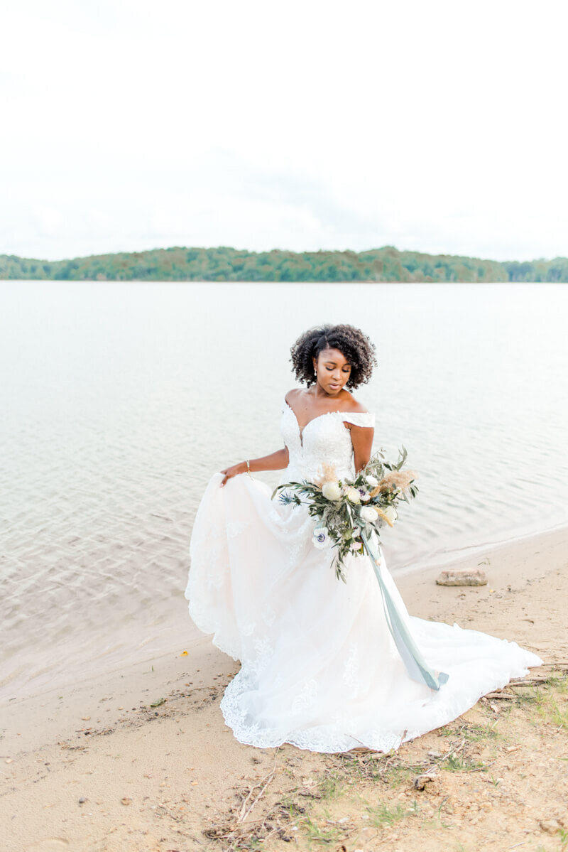 Trendy bride styled photo of bride wearing essense of australia dress in style Style D2815 holding bouquet with ocean background