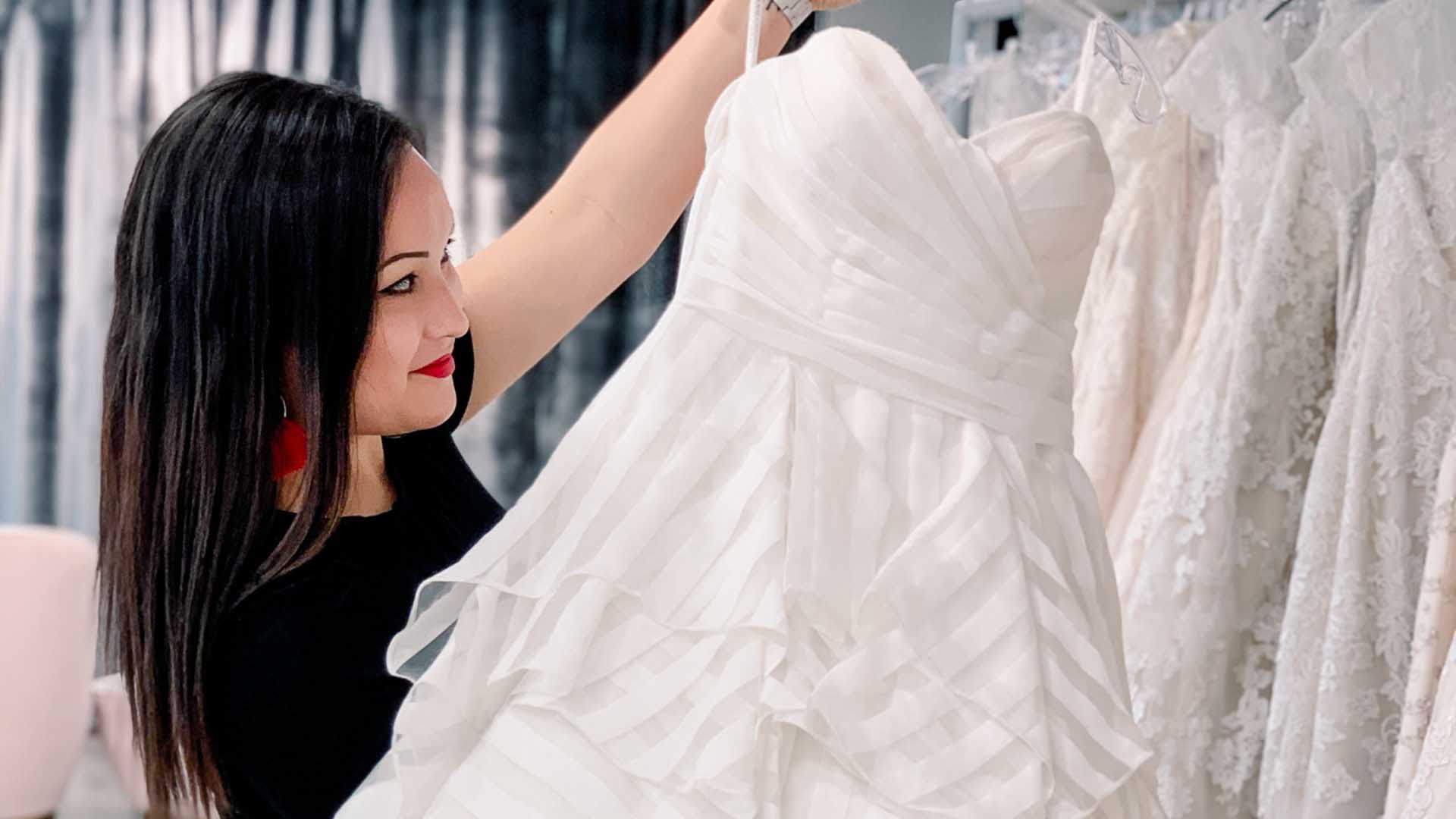 Expert stylist at true society by belle vogue bridal holding wedding gown