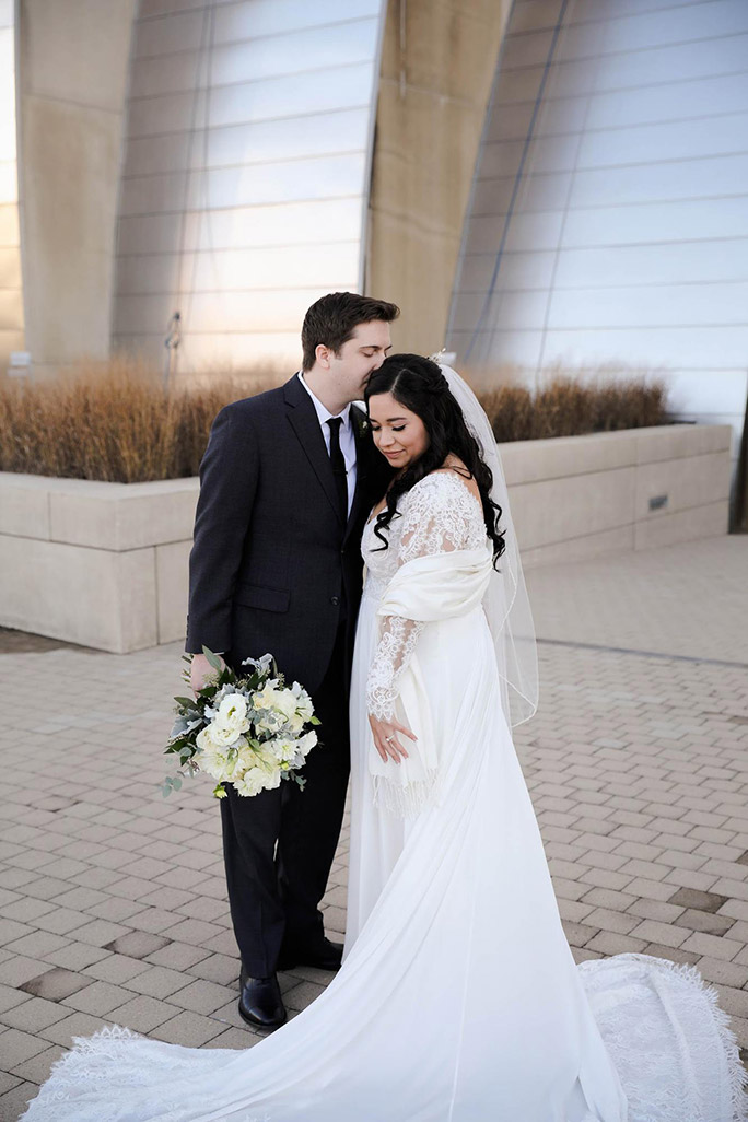 true bride julia posing for wedding photos outside of the Kauffman Performing Arts Center in KC
