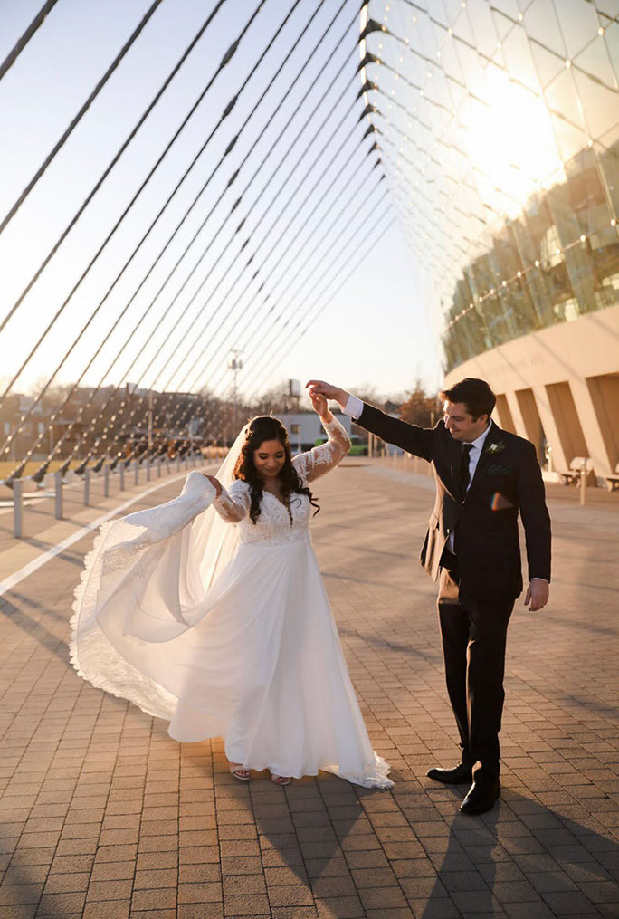 True bride Julia and husband greg holding hands and dancing outside the Kauffman Center in Kansas City