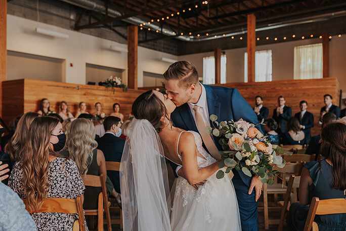 real bride and husband sharing kiss at wedding venue - style D2840 by essense of australia