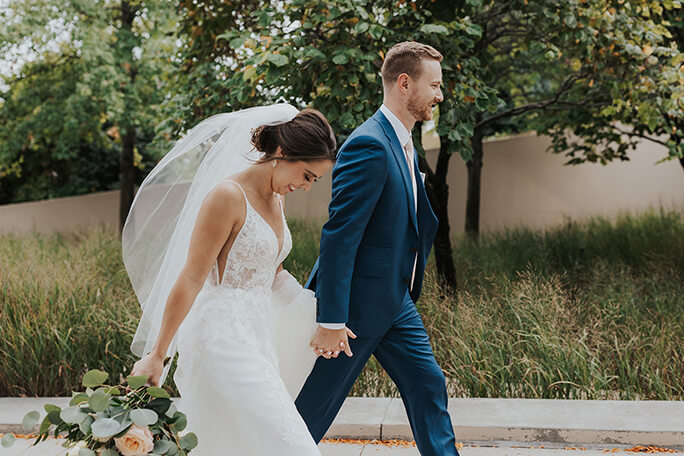 real bride Katie and husband holding hands - style d2840 by essense of australia