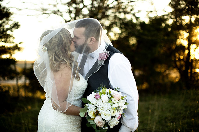 real bride and groom sharing a kiss - style D2174 by essense of Australia